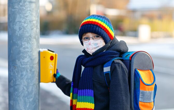 Little kid boy with glasses wearing medical mask on the way to school. Child backpack satchel. Schoolkid on winter day with warm