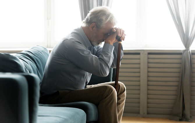 Unhappy old man with cane feel lonely at home